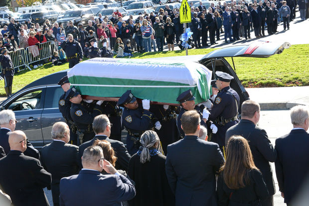Sgt. Paul Tuozzolo's casket is carried out of his hearse outside St. Rose of Lima church in Massapequa, Long Island.