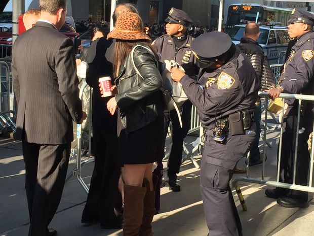 NYPD examine the backpack of a woman before she crosses the security checkpoint leading to Trump Tower on Fifth Avenue and 56th Street.