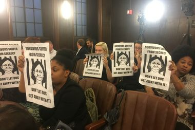 After the Board of Corrections vote passing new rules addressing sexual violence in jails, the transgender advocates in the meeting room held up signs in silent protest.