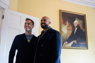 Nicholas Christopher and Mikah Meyer pose in front of a portrait of George Washington at Alexander Hamilton's Harlem home.