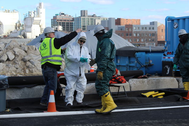 Christos Tsiamis, the EPA's remediation project manager for the Gowanus Canal, suited up in white hazmat gear to examine debris removed recently from the canal. The new buildings in the backbround are luxury rental apartments on the banks of the heavily polluted canal.