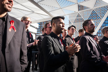 The Gay Men's Chorus waits to perform at the unveiling, framed by the memorial.