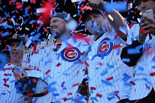 Jon Lester holds the Commissioner's Trophy while embracing Anthony Rizzo last year during the World Series championship rally in Grant Park.