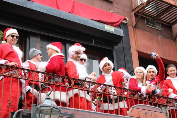 Santas celebrate on the balcony of Professor Thom's in the East Village during SantaCon 2016.