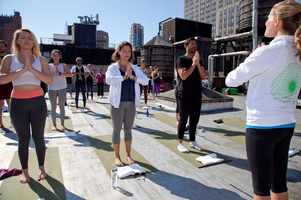 A rooftop yoga class run by hOM, which runs classes in buildings, including in unused spaces