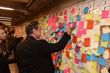 Gov. Andrew Cuomo places a Post-It Note message on a wall at Union Square on Nov. 14.