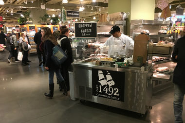 A worker prepares pricey chopped cheese sandwiches at the Whole Foods in Columbus Circle, an act of