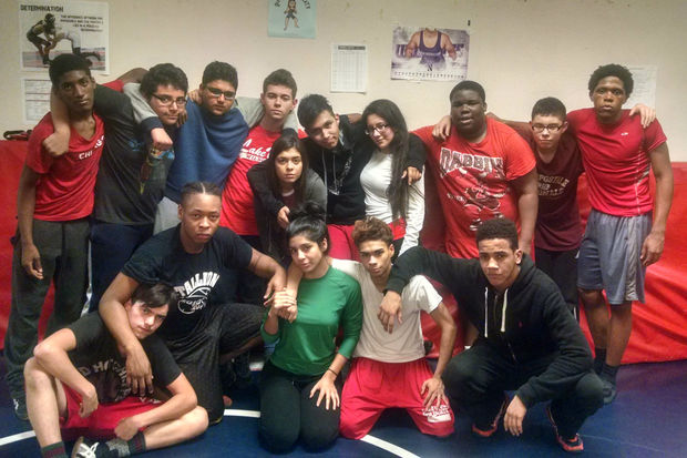 The Lake View High School varsity wrestling team features three girls: Dulce Reyes (in white shirt in back row), Vanessa Munoz (in maroon) and Daniela Garcia (in green).