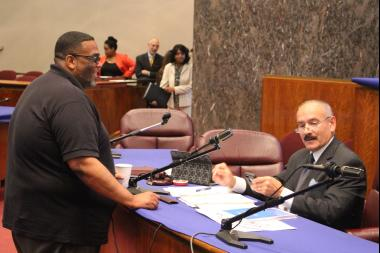 Aldermen Christopher Taliaferro and Ariel Roboyras talk before Wednesday's hearing on police accountability.