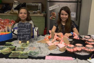Two elementary school children sell crafts like homemade candy and bracelets at the Ridgewood Kid's Market in the Ridgewood YMCA.