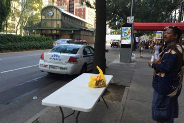 Book seller Kirk Davidson stands in front of an empty table on Broadway next to an NYPD cruiser.