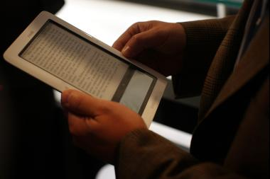 A person reads a text from a NOOK e-reader.