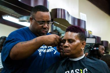 A patron gets a haircut at the annual health fair at Denny Moe's Superstar Barbershop in Harlem.