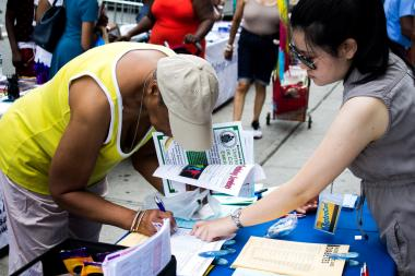 A community member in Harlem gets information from one of the dozens of health booths set-up at the annual health fair at Denny Moe's Superstar Barbershop.