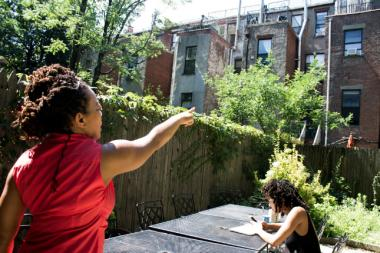 Nia Bediako points to her neighbor's house, which was recently visited by a raccoon and frightened their children.