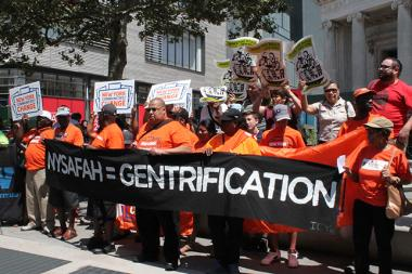 Affordable housing advocates marched between luxury developments Wednesday in Downtown Brooklyn protesting the use of private developers to build affordable housing on public land.
