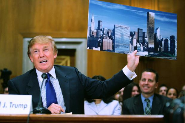 Donald Trump holds a photo of his 90-floor building the Trump World Tower,