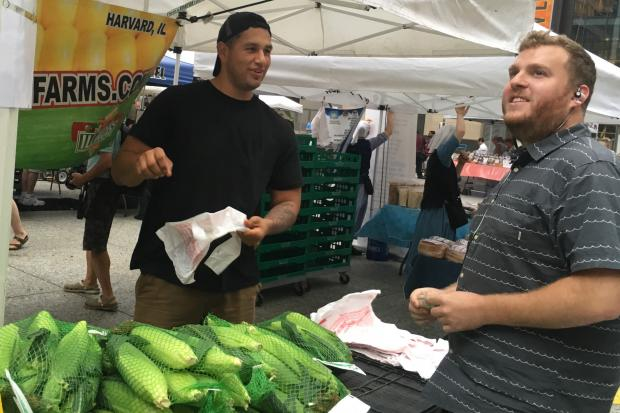 Patrick Land (right) buys sweet corn from Cesar Flores, an employee of Twin Garden Farms that produces a popular brand of sweet corn.