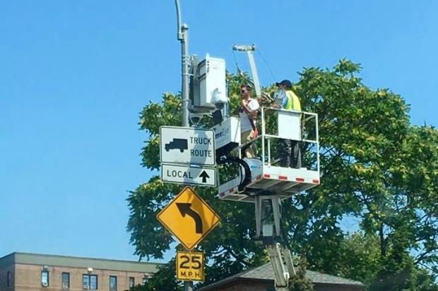 A crew installing an NYPD security camera at the corner of Park Lane South and Woodhaven Boulevard near Forest Park.