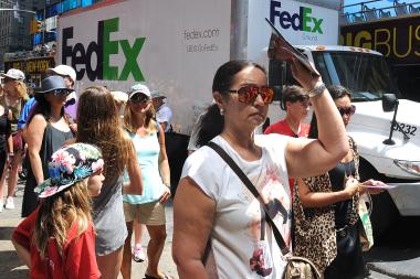 A woman waiting for a tour bus on Seventh Avenue tried to shield her face from the sun.