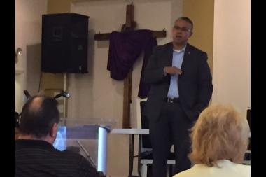 Ald. Gilbert Villegas talks with residents at Word of Life Church of God Thursday evening.