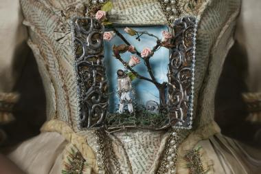 Fabiola Jean-Louis' painting depicts a black man hanged from a tree, contained within a frame positioned over the stomach of a white dress draped in paper flowers, pearls and chains.
