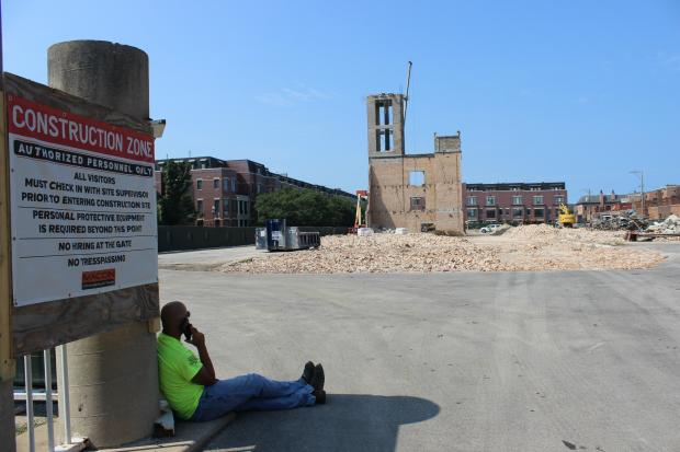 A construction worker sitting near what's left of the old Tag Outlet building, which is being replaced with a 76-unit development.
