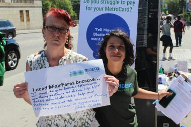 Marie Whalen (L) holds up a sign detailing her difficulties affording a MetroCard next to Riders Alliance Campaign Manager Rebecca Bailin (R).