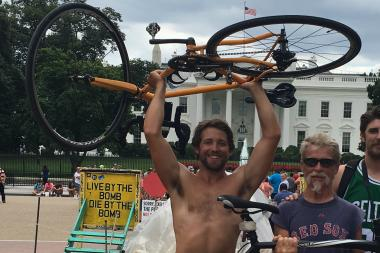 Chicago's Tommy Schneider holds up his bike in celebration after completing a cross-country bike ride. His dad, Tom (in sunglasses) rode 1,800 miles with him, and his brother, James (partly pictured) helped provide support transportation.