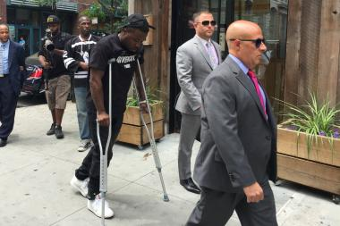 Rapper Troy Ave walks on crutches with his lawyer Scott Leemon (right) before announcing a lawsuit against Irving Plaza on Monday. He is wearing a a GPS monitor on his right ankle as part of a $500,000 bail agreement.