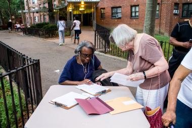 Residents sign petitions, which will be delivered to the Board of Elections, calling on the agency to reinstate a polling site for senior and disabled residents.