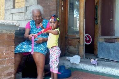 Katie Brown, 99, sits on her front porch with her great-great-granddaughter London, 2.