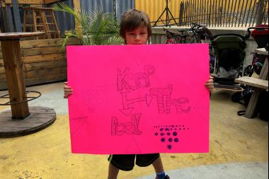 Izzy, 6, stands with a sign at the rally for the pop-up pool.