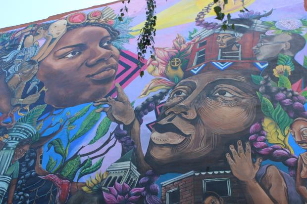 A new mural but the non-profit Groundswell went up at Mama Dee's Garden in Crown Heights this week. The mural depicts women of color, specifically women of Afro-Caribbean heritage, with young people.