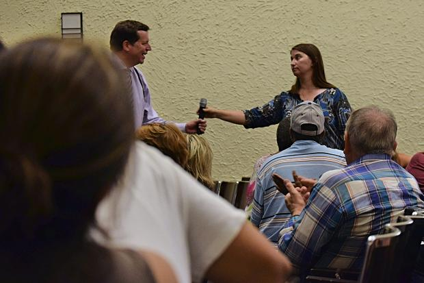Ald. Joe Moore (49th) takes the microphone back from parent Rebecca Weinberg after speaking at Tuesday night's meeting.