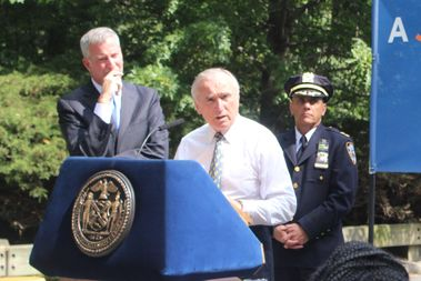 Police Commissioner Bratton, center, speaks about preparation for J'Ouvert with Mayor de Blasio, left, and Chief Steven Powers of Brooklyn South in Prospect Park on Wednesday.