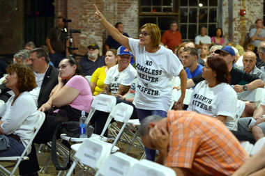 A woman yells up at Commissioner Steve Banks at a meeting for a proposed homeless shelter in Maspeth, Queens on Aug. 31.