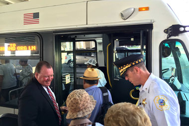 Ald. Patrick D. Thompson (11th) and Deering District Police Cmdr. Daniel Godsel welcome 11th Ward residents onto the reinstated No. 31 bus.