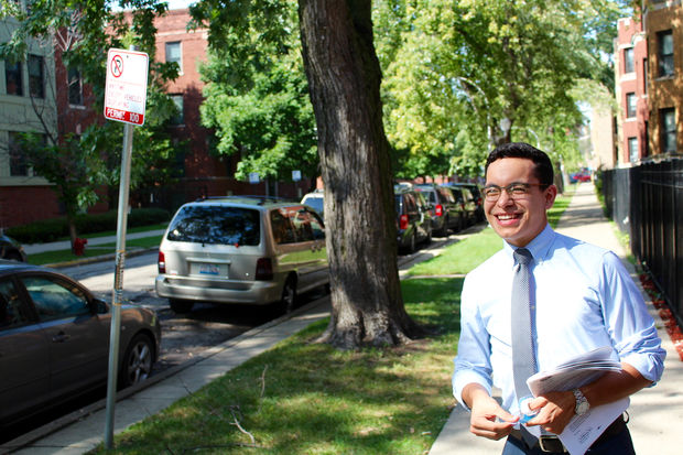 Anthony Quezada, a constituent services advocate in the 35th Ward, posts flyers Wednesday afternoon about the zone changes in Logan Square .
