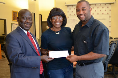 Kofi Boateng (left) hands the check to Maritta Dunn (center), chair of the Manhattanville Houses and General Grant Houses Benefit Committee and Leroy Williams, Deputy Director of NYCHA's Manhattan Community Operations.
