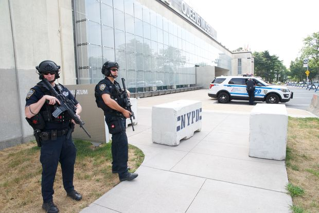 Two NYPD officers carrying machine guns stand in front of the Queens Museum on Thursday, Sept. 8, 2016, during the U.S. Open.
