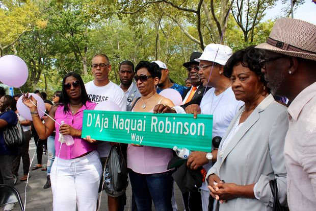 Family members and elected officials pose with the street sign in D'Aja Naquai Robinson's name.