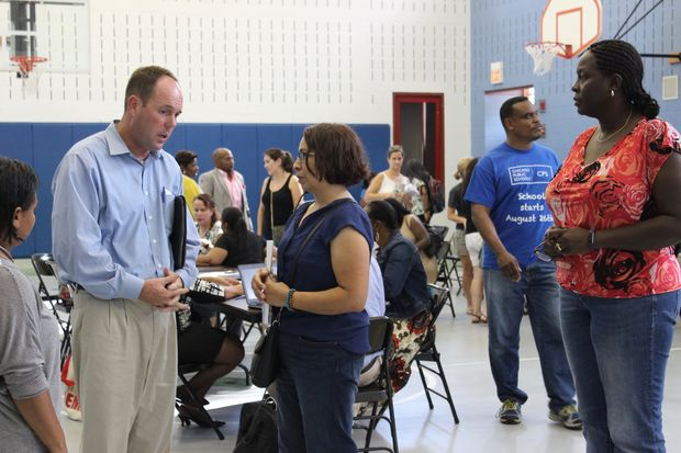 Ald. Matt O'Shea (19th) speaks with parents after the Local School