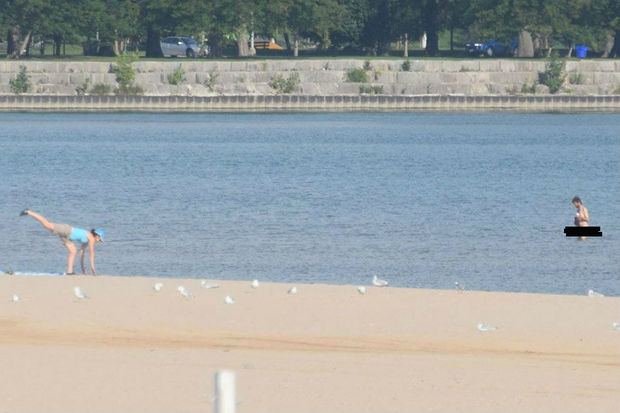 A nude beachgoer chills in the water at Montrose Beach while a woman exercises.