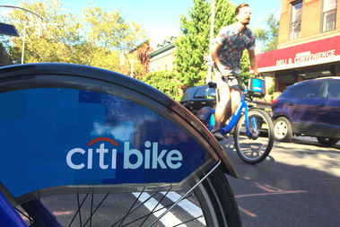 A Citi Bike rider rolls past a station at Henry and Degraw streets in Carroll Gardens.