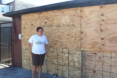 Claudia Lucero stands in front of her family's garage near 22nd Place and Leavitt that was destroyed in a fire early Tuesday.