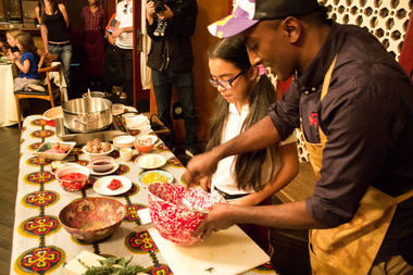 Marcus Samuelsson gives a hands-on lesson to a student from Lexington Academy .