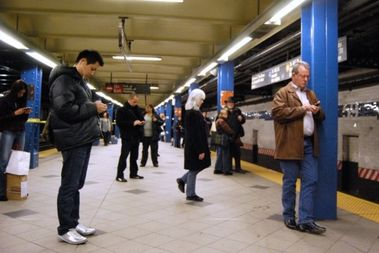 Straphangers use their phones on the station platform at 59th Street.