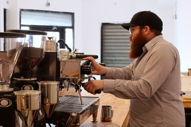 Zalmy Mochkin, proprietor of the Dean Street Cafe, makes and espresso for a friend at his new cafe at 87 Utica Ave. in Crown Heights.