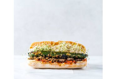 The vegan zucchini falafel sandwich combines miso-charred zucchini, mushroom falafel, hummus, sprouts, and lemon tahini on ciabatta.